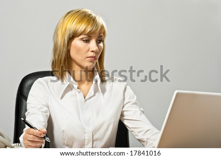 Young beautiful business lady at a table with a laptop.