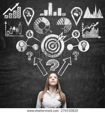 Young beautiful business lady is thinking about strategy development process of the business. Drawn chalk flowchart on the dark wall. - stock photo