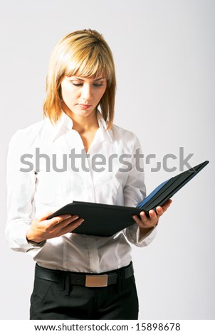 Young beautiful business lady with a folder reading.
