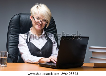Young beautiful business lady works on laptop in office - stock photo