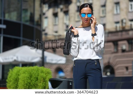 Young beautiful business woman calling by phone