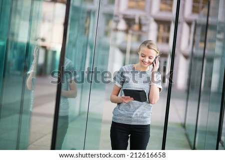 Young beautiful business woman in modern glass interior speaking on the phone and using tablet