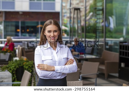 Young beautiful business woman in white shirt on summer street