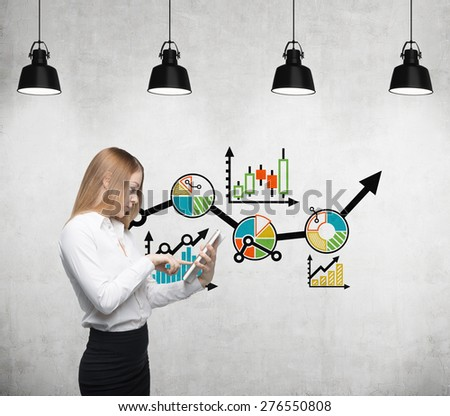 Young beautiful business woman is thinking about business optimisation process by working on the tablet. Drawn colourful business flowchart on the concrete wall. - stock photo