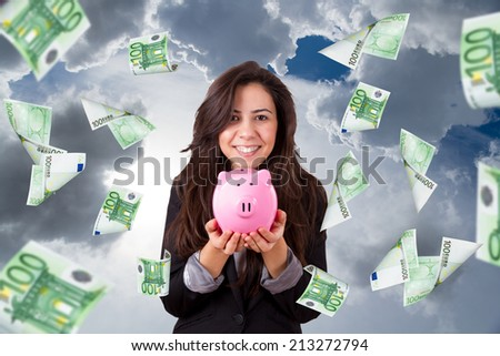 Young beautiful business woman smiling, holding and showing pink piggy bank, hundred euro banknotes flying around pretty girl. - stock photo