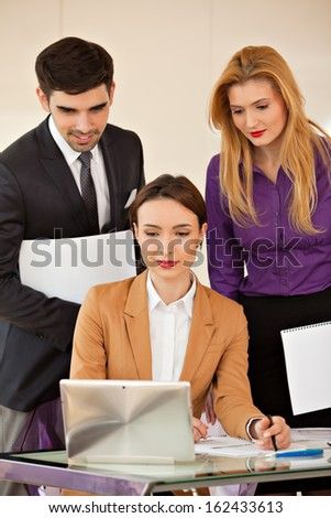 Young beautiful business woman smiling, looking at laptop and two colleagues business people in the back