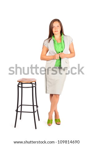 Young beautiful business woman stands near tall stool in studio on white background. - stock photo