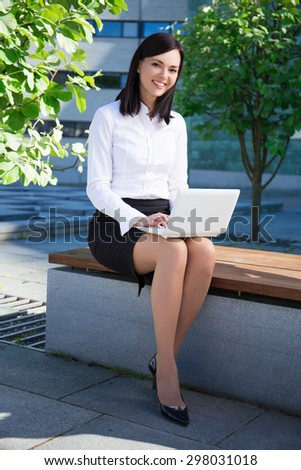 young beautiful business woman using laptop in city park - stock photo