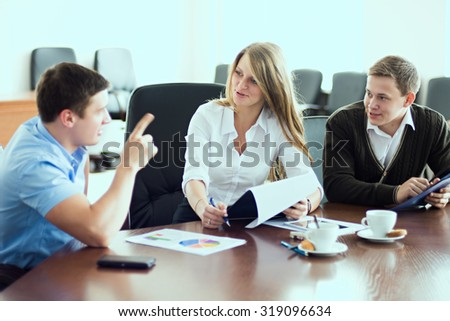 Young beautiful business woman with business partners, men at a business meeting. - stock photo