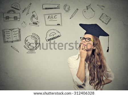 Young beautiful business woman with graduation hat looking up thinking about education isolated on gray wall background  - stock photo