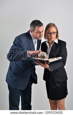 Young beautiful business woman with male colleague reading a book - stock photo