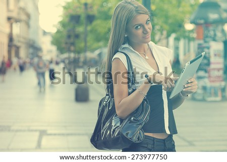 Young Beautiful Business Woman with tablet computer walking on urban street, downtown - stock photo