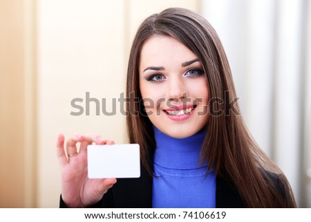 Young beautiful businesslady holding a blank card - stock photo