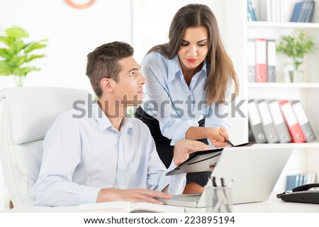 Young beautiful businesswoman and businessman working on laptop in the office.
