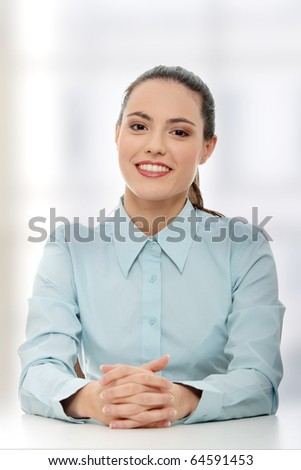 Young beautiful businesswoman behind the desk - stock photo