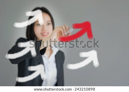 Young beautiful businesswoman drawing rising arrows - stock photo