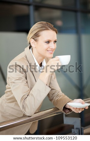 young beautiful businesswoman drinking coffee - stock photo