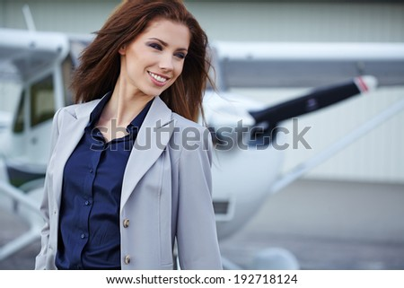 Young beautiful businesswoman  in front of airplane.