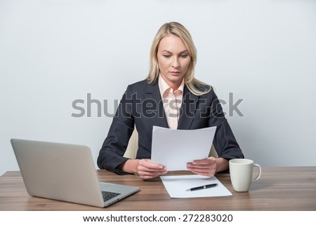 Young beautiful businesswoman is reviewing legal documents. - stock photo