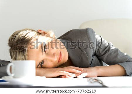 Young beautiful businesswoman is sitting in the office. Break time with cup of coffee - stock photo