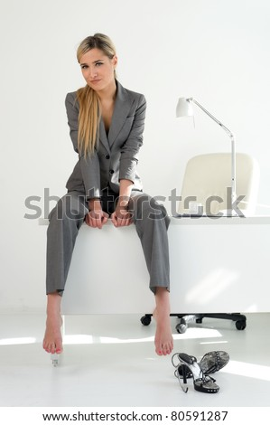 Young beautiful businesswoman is sitting on the table in the office. Break relaxing time - stock photo