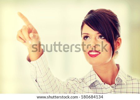 Young beautiful businesswoman making choose on abstract screen - stock photo