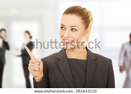 Young beautiful businesswoman pointing up. - stock photo