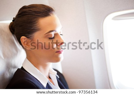 young beautiful businesswoman resting on airplane - stock photo