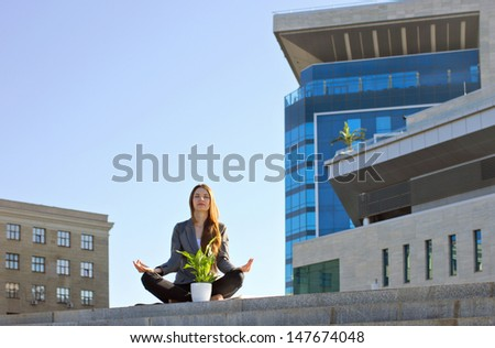 young beautiful businesswoman sitting in yoga pose lotus outdoor, on building and sky background - stock photo