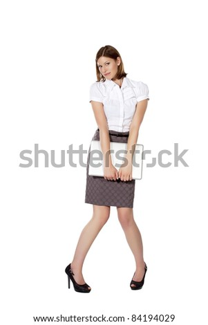 Young beautiful businesswoman standing and holding notebook in both hands - stock photo
