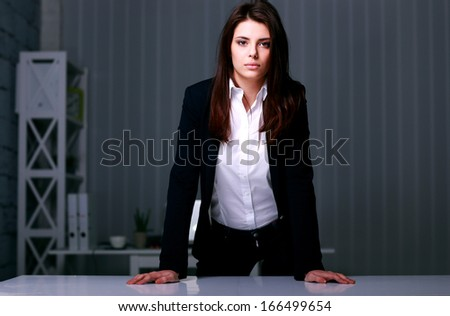 Young beautiful businesswoman standing near the table in office - stock photo