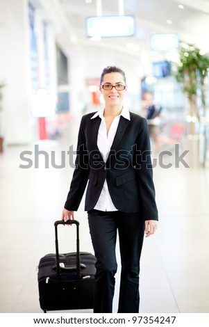 young beautiful businesswoman walking in airport with luggage