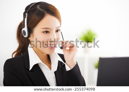 young beautiful businesswoman with headset in office - stock photo
