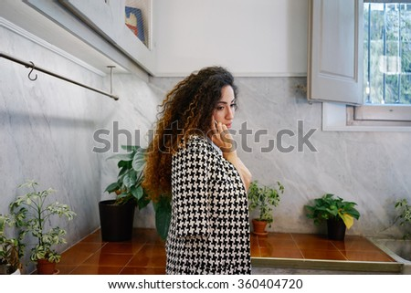 Young beautiful businesswoman with long curly hair talking on cell telephone.brunette Caucasian girl talking on smart-phone in coffee-shop - stock photo