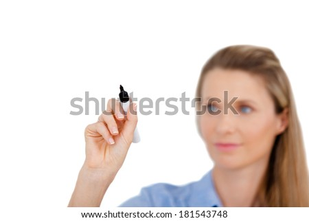 Young beautiful businesswoman with pen writing on a screen / whiteboard. Focus on the black marker - lot's of copy space. Blond hair caucasian model isolated on seamless white background. - stock photo