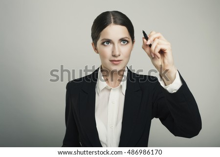 Young beautiful businesswoman with pen writing on the screen
