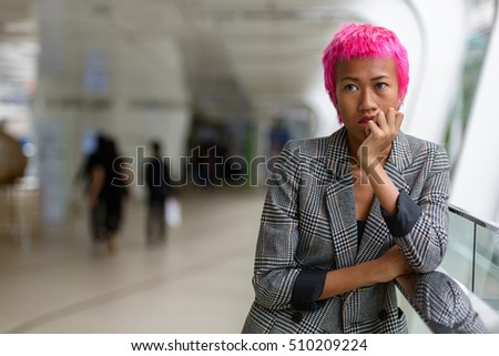 Young beautiful businesswoman with pink hair thinking in city