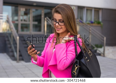 Young beautiful businesswoman writing a message on smartphone after work - stock photo