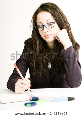 Young beautiful businesswoman writing in notebook