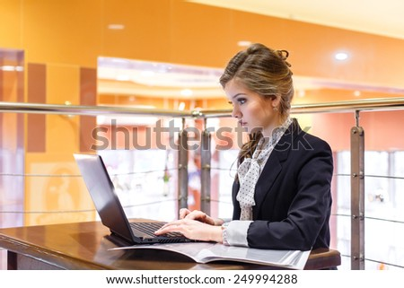 Young beautiful businesswomen sitting in a cafe and working on a laptop - stock photo