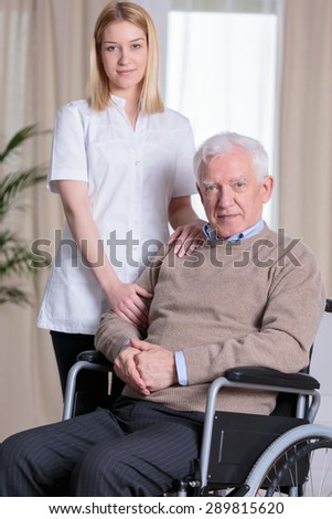 Young beautiful caregiver and older disabled man on wheelchair - stock photo