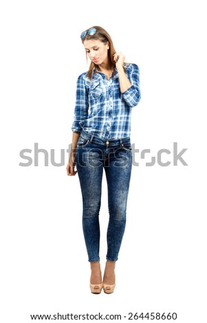 Young beautiful casual female fashion model looking down. Full body length portrait isolated over white background - stock photo