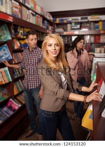 young beautiful caucasian blonde girl standing in a bookshop in front of a shelf with other people in background