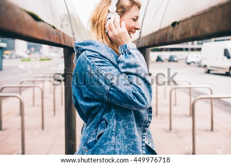Young beautiful caucasian blonde woman listening music with headphones smiling outdoor in the city - happiness, relaxing, music concept - stock photo