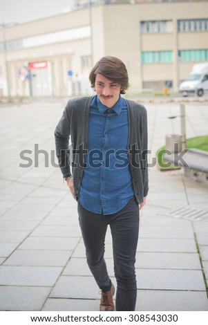 Young beautiful caucasian brown hair man with moustache walking posing through the streets of the city overlooking left smiling - Freshness, serene, carefreeness concept