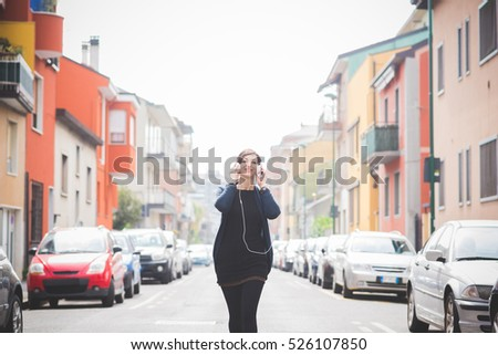Young beautiful caucasian brown hair woman outdoor in the city listening music with head phones, and smart phone hand hold - technology, music, relaxing concept