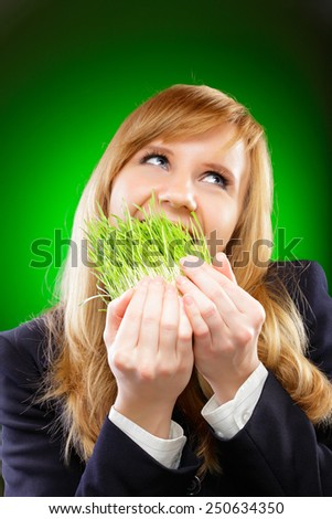 Young beautiful Caucasian business woman head and shoulders studio shot on green background. Looking up, biting green spring grass.  - stock photo