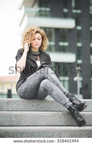 Young beautiful caucasian contemporary businesswoman seated on the stairs talking smartphone and using a tablet looking the screen- technology, network, business, finance concepts - stock photo