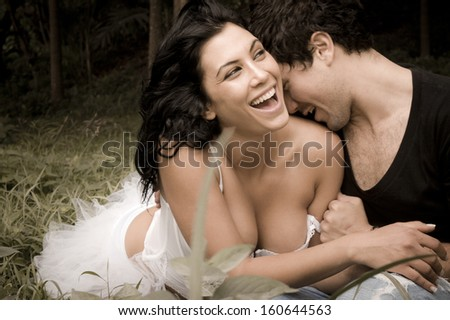 Young beautiful caucasian couple in forest sharing a happy moment