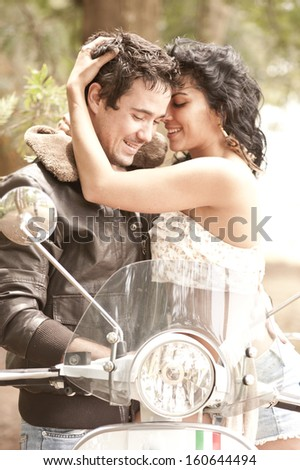 Young beautiful caucasian couple sharing an intimate moment on a white scooter bike - stock photo